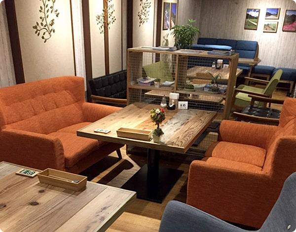 画像:室内にソファーとテーブルが複数あり。青とオレンジのゆったり座れるソファになっている。